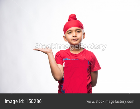 Portrait of Indian Sikh/punjabi little boy presenting while standing isolated over white background