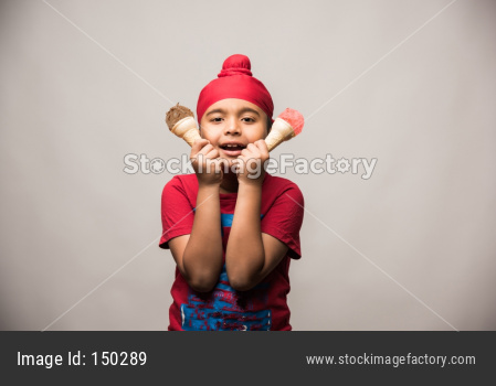 cute little Indian sikh/punjabi boy eating ice cream in cone