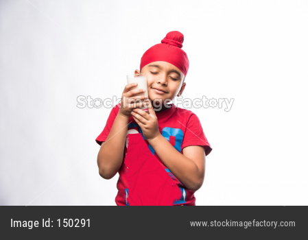 Indian Sikh/punjabi small boy holding a glass full of milk, isolated over white background