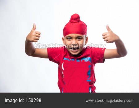 Portrait of Indian Sikh/punjabi little boy showing thumbs up / success sign while standing isolated over white background