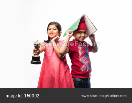 Indian  sikh / punjabi small girl and boy standing with a book and Victory trophy - education and success concept