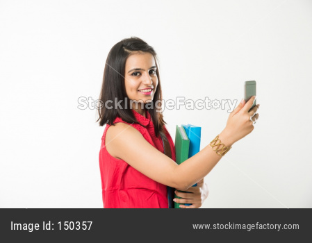 Pretty Indian/Asian College Girl holding books and clicking selfie with smartphone, standing isolated over white background