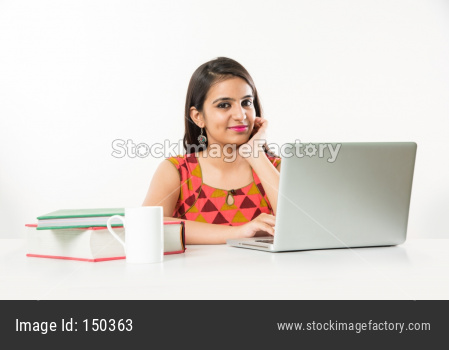 Pretty Indian/Asian Girl studying on laptop computer with pile of books on table, over white background