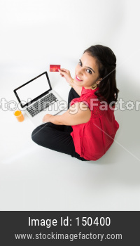 Girl online shopping using debit/credit card on laptop computer
