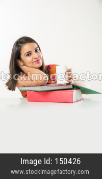 Pretty Indian/Asian collage Girl studying on tablet with pile of books
