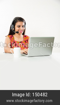Pretty Indian/Asian Call Centre employee speaking using headphone while sitting with laptop, against white background