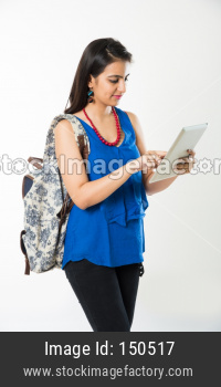 Pretty Indian/Asian young college Girl with Bag using Tablet Computer, Standing isolated against white background
