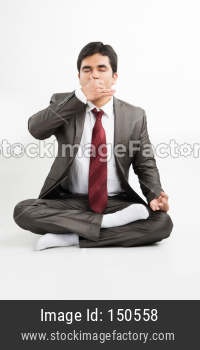 Indian young businessman doing yoga / pranayama / exercise