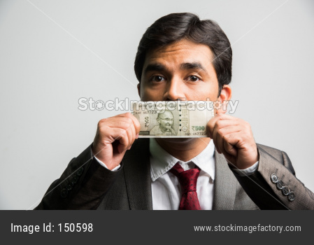 Indian young businessman bribing concept with paper currency covering mouth