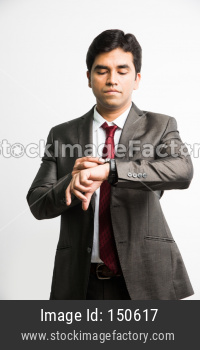 punctual Indian young businessman setting wrist watch / clock