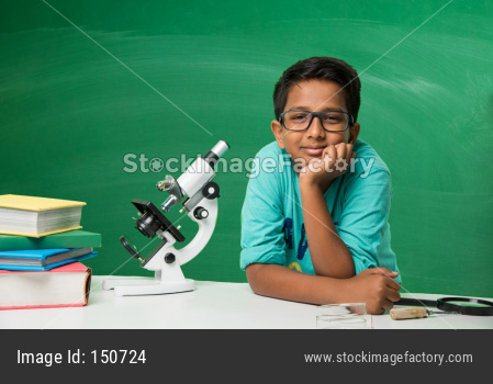 small boy studying science in classroom against green chalkboard background with science doodles