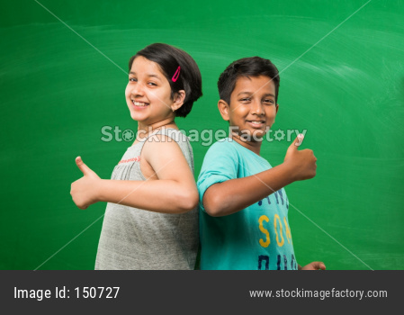 Little school kids standing in front of green chalk board with doodles - education and kids concept
