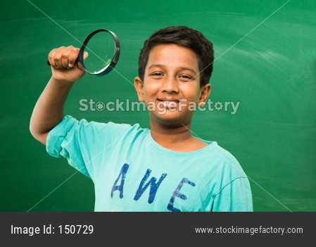 Little school boy standing in front of green scalk board with doodles - education and kids concept