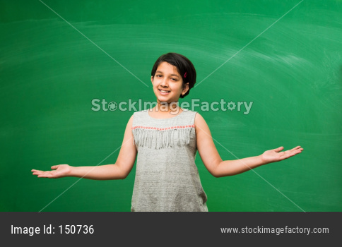 Little school girl standing in front of green scalk board with doodles - education and kids concept