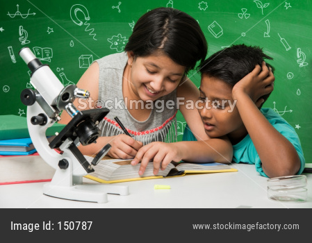 small boy and girl studying science in classroom against green chalkboard background with science doodles