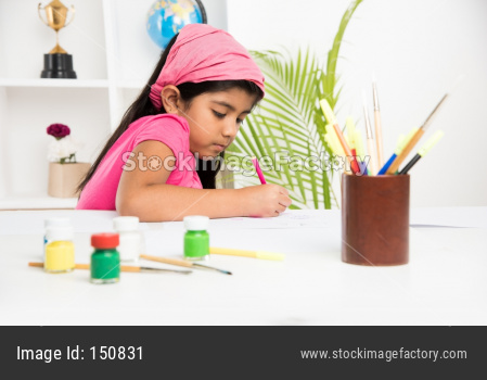 Cute Little Indian/Asian girl child enjoying drawing OR painting with brush and paint over paper at home