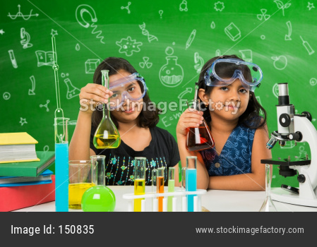 little girls studying science in classroom against green chalkboard background with science doodles