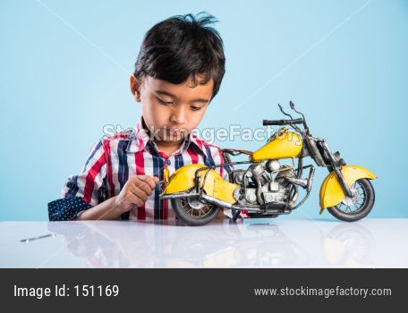 cute little kid mechanic trying to fit toy motor bike