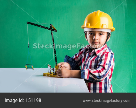 Cute little indian boy playing with toy crane