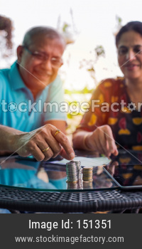 Senior Indian/asian couple arranging/staking coins pile in a row, selective focus
