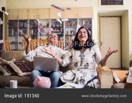 Happy Senior Indian/asian couple having won lottery or investment earning in form of Money/paper currency falling from sky / rai