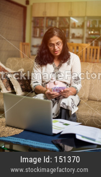 Senior Indian/asian lady/women accounting with cash and laptop at home, selective focus