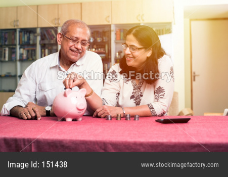 Senior Indian/asian couple accounting, doing home finance and checking bills with laptop, calculator and money while sitting on