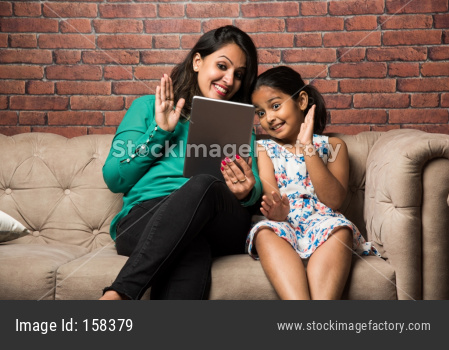 Indian mother and daughter on video call using using tablet computer, waving hands while sitting on sofa/couch