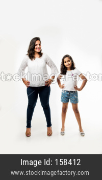 Indian small girl and mother standing over white background measuring height difference