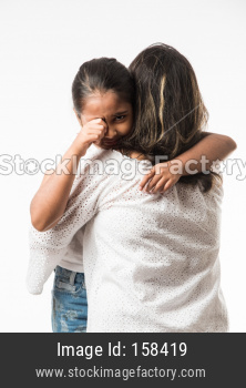 Indian girl crying in mother's arms over white background