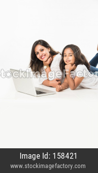 Indian mother and daughter lying on floor with book, laptop or tablet computer studying or readying story or playing games
