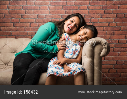 Indian mother and daughter on sofa, cuddling, tickling, selective focus