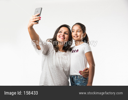 Indian/asian mother daughter taking selfie picture with smartphone, isolated over white background