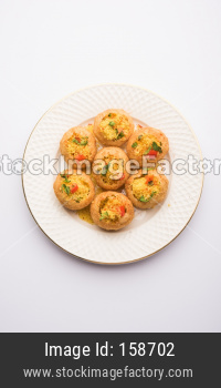 Aloo Sev Puri is a popular Indian roadside chat item, served in a white plate. Top view, selective focus