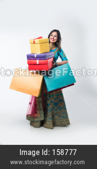 Indian girl with Shopping bags and gift boxes, standing isolated over white background