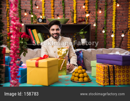 Indian man sitting with gifts and sweets on sofa/couch