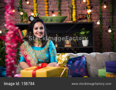 Indian girl/female sitting with gifts and sweets on sofa/couch