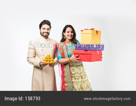 Indian couple with sweets and gift boxes