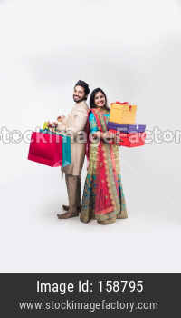 Indian couple with shopping bags and gift boxes on wedding day or diwali , standing isolated over white background