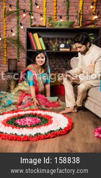 Indian couple making flower Rangoli on Diwali or Onam Festival, taking selfie or holding sweets