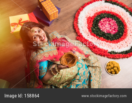 beautiful indian girl holding diya on diwali festival night, top view.selective focus