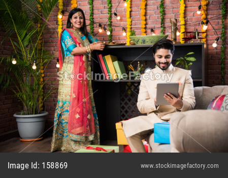 Indian man using tab / touchscreen computer and wife lighting diyas in the background on Diwali festival day