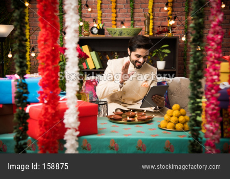 Indian man using tablet touchscreen computer on festival day while wearing traditional outfit. sitting on sofa with gifts and sw