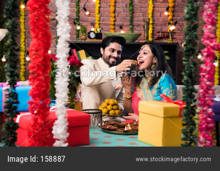 Indian smart couple eating sweet laddu on Diwali or anniversary, selective focus