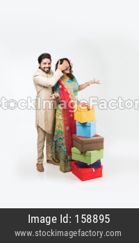 Indian Man giving surprise gift to wife, standing isolated over white background