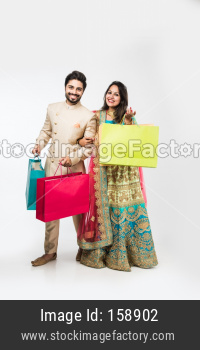 Indian couple with shopping bags in ethnic wear, standing isolated over white background. selective focus