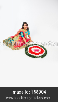 girl/woman making flower rangoli for hindu festival celebration, sitting over white background, selective focus