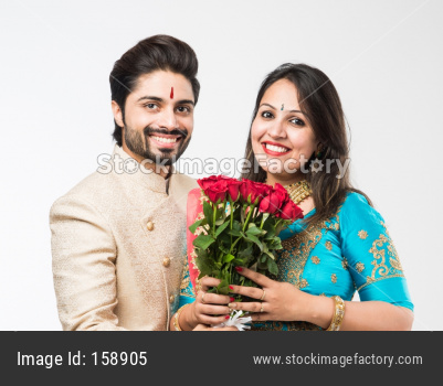 Indian Man giving rose flowers bouquet to wife, standing isolated over white background