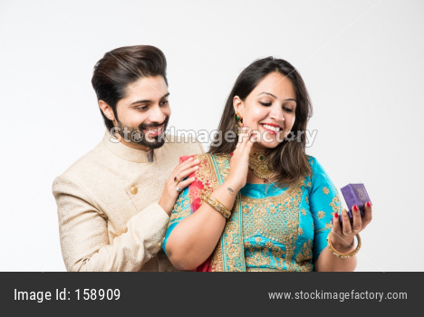Indian Man giving surprise jewellery gift to wife, standing isolated over white background