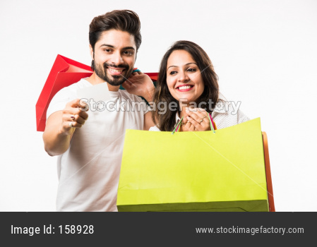 Indian young couple shopping bags and locating store, standing isolated over white bac